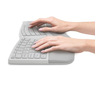 Fingers typing on built-in wrist rest ergonomic keyboard